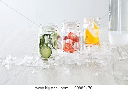 Closeup Rustic Jars With Ice And Various Fillings: Orange,strawberry,cucumber And Mint Prepared To M