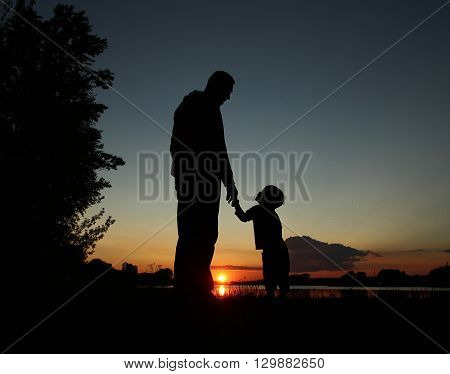 father and son silhouette on sunset very nice
