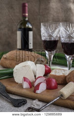 Bottle of wine cheese vegetables and white bread are on sacking