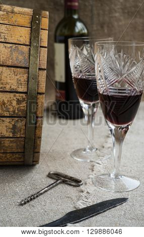 Octave bottle and two wineglasses are on sacking