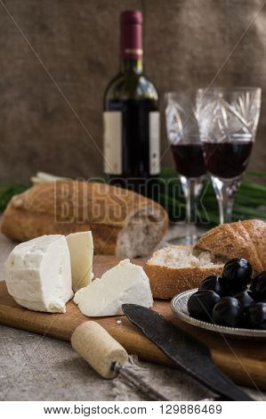 Bottle of wine olives cheese and white bread are on sacking