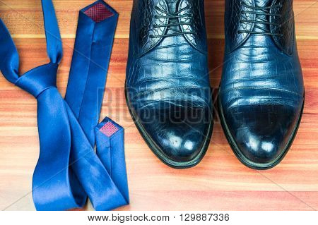 Classic men shoes and blue tie on wood background
