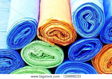 A lot of colorful garbage bags rolls