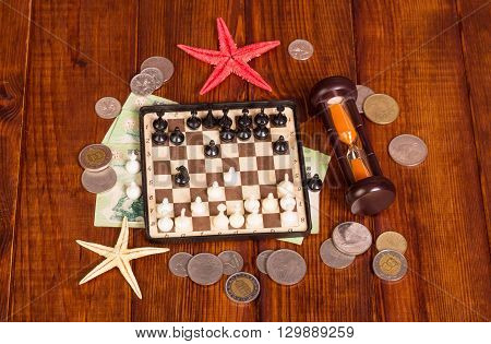 Accessories for the traveler: chess, hourglass money against the dark wood.