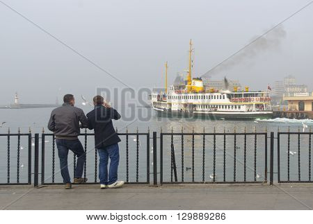 Istanbul Turkey - January 5 2014: Istanbul dense fog in the throat was found to affect the transportation and daily life. Two young men watching foggy conditions in the harbor.