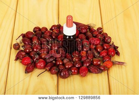 The essential oil in a glass bottle and rose hips on a background of light wood.