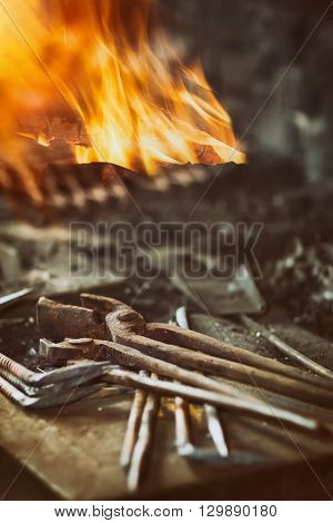 Blacksmith tools in the background with fire