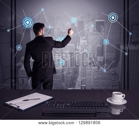 An elegant businessman connecting blue circle dots on urban city scape background concept at an office desk in a conference room
