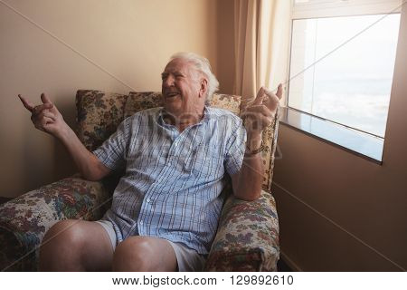 Indoor shot of happy old man sitting on a arm chair and smiling. Senior man relaxing at old age home.