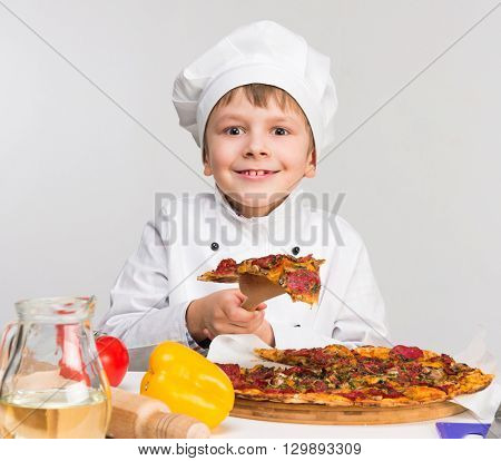 funny little boy in cook uniform holding a piece of tasty pizza