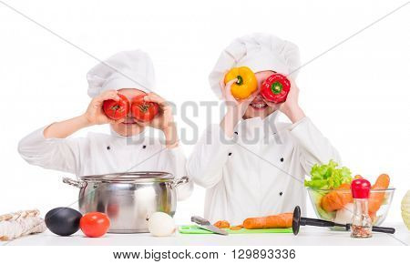 two little cooks in uniform playing vegetables for soup in the kitchen