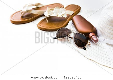 Beach accessories. Summer shoes and hat with sunglasses and suntan lotion on a white background