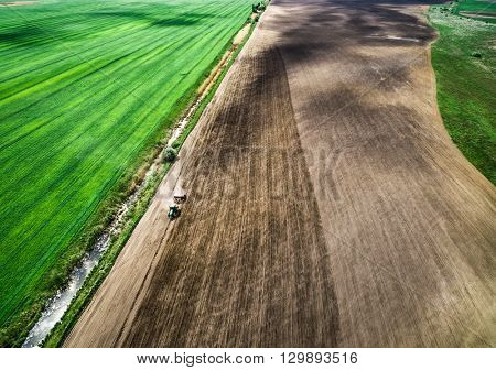 harvester plowing field in spring, view from height