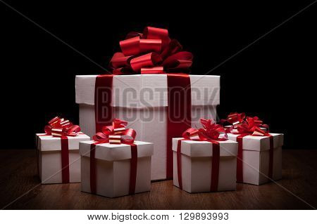 one large white gift box with small gift boxes on black background