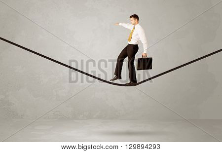 An elegant businessman in suit balancing on a tight rope with a briefcase in front of grey urban wall background environment concept
