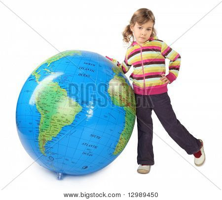 little girl standing near big inflatable globe, thrust out one leg, isolated on white