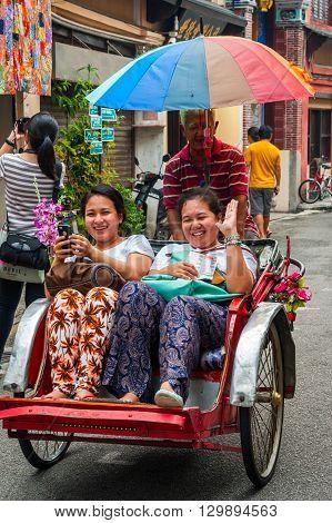 Man Riding Rickshaw With Two Women