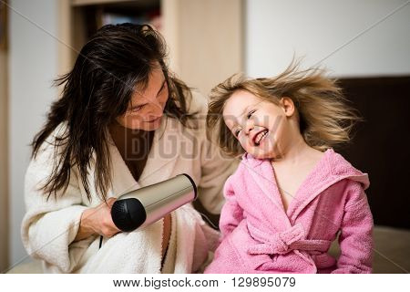 Mother and her little daughter having fun with hairdryer