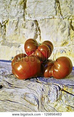 Big Black Heirloom organic tomatoes on wooden and stone background