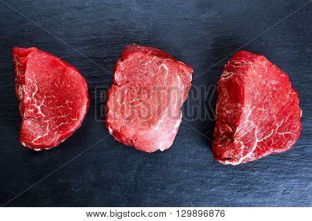 Fresh Raw Beef steak Mignon on blue dark board background. ready to cook