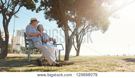 Retired Couple Relaxing Outdoors On A Bench