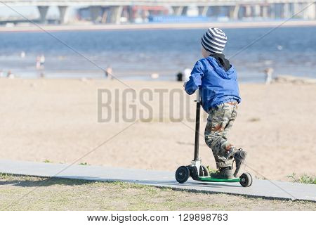 Sankt-Petereburg, Russia - May 15 2016: the boy rides the scooter from hills. In St. Petersburg in parks many people are engaged in active sports
