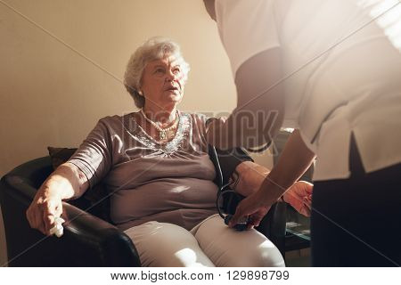 Nurse Measuring Blood Pressure Of Her Senior Patient