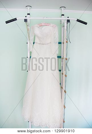 Modern white wedding dress hanging on the hanger