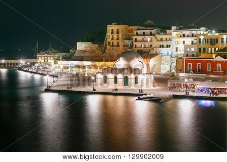 Picturesque view of Venetian quay of Chania with Kucuk Hasan Pasha Mosque at night, Crete, Greece