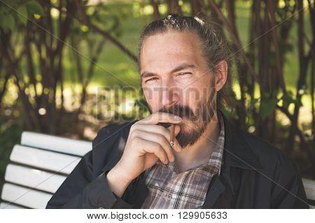 Bearded Man Smoking Cigar In Summer Park