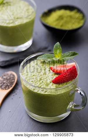 Matcha green tea chia seed pudding, dessert with fresh mint and strawberry on a black slate background. Healthy breakfast