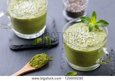 Matcha green tea chia seed pudding, dessert with fresh mint and coconut on a black slate background. Healthy breakfast
