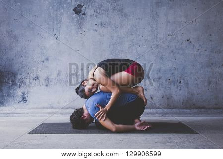 Male and female practicing yoga stretches together