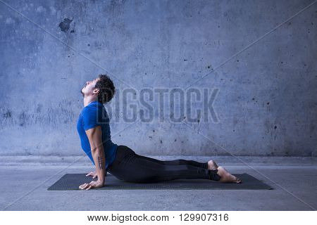 Young man practicing yoga. Upward facing dog, or urdhva mukha svanasana.