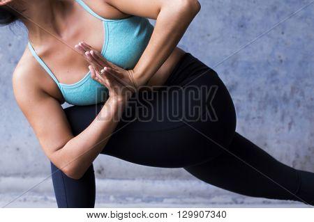 Young woman practicing yoga. Parsvakonasana, side angle pose.