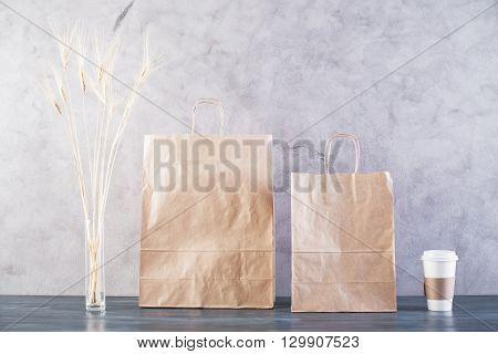 Two take away food bags wheat spikes and coffee cup on concrete background. Mock up