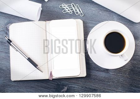 Topview of blank smartphone and notepad with pen on dark wooden desktop with coffee cup clips and other items. Mock up