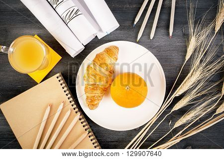 Top view of wooden desktop with orange and croissant on plate juice stationery wheat spikes and paper rolls