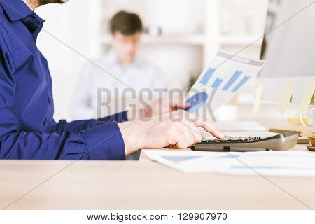 Sideview of businessman using calculator on business charts