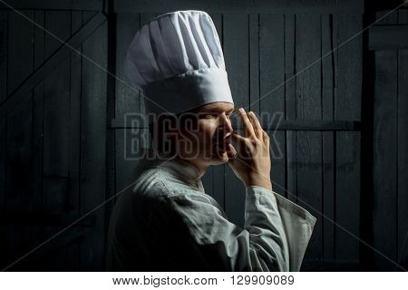 Professional chef in white hat with taste approval gesture