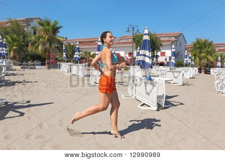 young woman smiling and running on beach near lounges and umbrellas, palms and houses