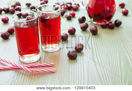 Left 2 glasses of juice, straws, scattered cherries, jar of cherry juice, on right empty space for text on green background. Cherries, cherry juice and empty space. Horizontal.