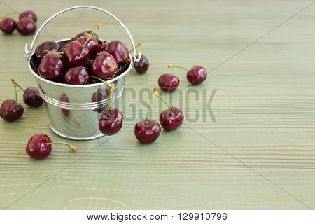 In the frame on the left a small bucket with cherries, around scattered cherries, on the right empty space on a light green background. Bucket of cherries. Horizontal. Daylight.