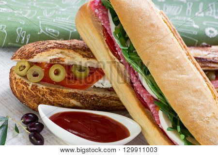 Diagonally lying sandwich with salami, mozzarella, arugula and tomato on sandwich with feta cheese, olives, tomato, near bowl with ketchup, a few olives on the background a green napkin.  Horizontal. Daylight.