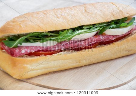 Diagonally lying sandwich with salami, mozzarella, arugula, tomatoes in front some space for text on the light wood background. Horizontal. Daylight. Close.