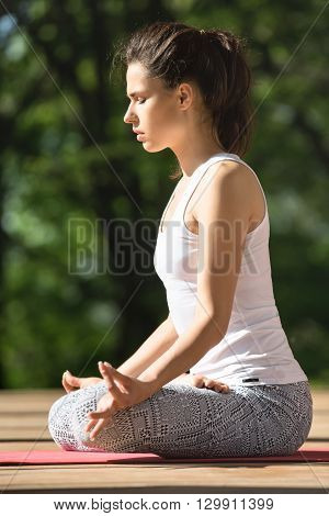 Cute girl with closed eyes is meditate in lotus pose on the wooden terrace on the nature background. She sits on the red yoga mat with her hands on the knees. Her index fingers and thumbs are together. She wears white sleeveless t-shirt and gray pants wit