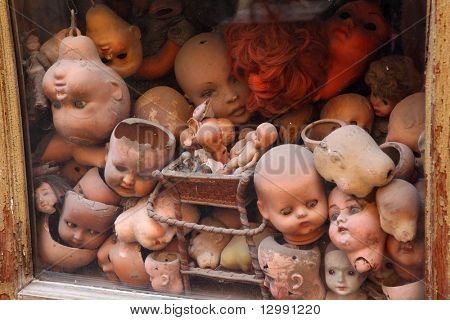 old showcase with many old heads dolls, red doll hair, several small dolls