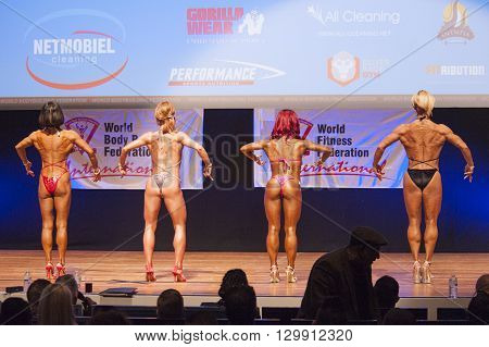 MAASTRICHT THE NETHERLANDS - OCTOBER 25 2015: Female fitness models Gerbel Mikk Sonja den Breems-Tanamal and two other competitors flex their muscles and show their best physique in a front back on stage at the World Grandprix Bodybuilding and Fitness