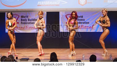 MAASTRICHT THE NETHERLANDS - OCTOBER 25 2015: Female fitness models Gerbel Mikk Sonja den Breems-Tanamal and two other competitors flex their muscles and show their best physique in a chest pose on stage at the World Grandprix Bodybuilding and Fitness