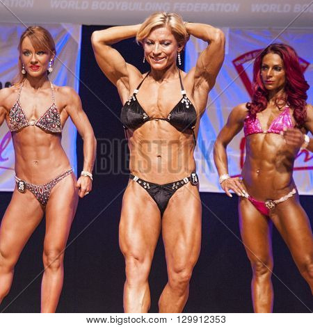 MAASTRICHT THE NETHERLANDS - OCTOBER 25 2015: Female fitness model Gerbel Mikk flexes her muscles and shows her best physique in a abdominal and thighs pose on stage at the World Grandprix Bodybuilding and Fitness of the WBBF-WFF